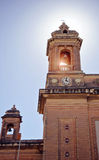 Bottom view of the two towers of the church with a bell and a cl. Ock on the blue sky background, Senglea Basilica, Malta Stock Photo