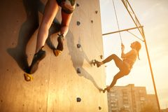 Bottom view of two young climbers practice on artificial climbing wall outdoors. Active sporty women compete on. Bottom view of two young climbers practice on Stock Photo