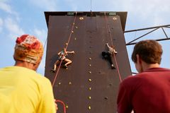 Bottom view of two young women climbers insured by men on rope belay harness approaching to finishing point on the speed Stock Photo