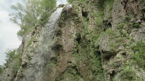 Bottom view of water stream falling from cliff. Slow motion bottom view of water stream falling from cliff stock video footage