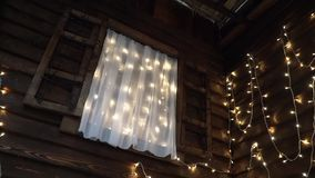 Bottom view on the window with shimmering garlands in a wooden house. Bottom view of a window with twinkling Christmas lights in a wooden house stock video
