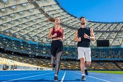 bottom view of young male and female joggers running on track stock photo