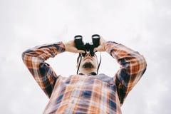 Bottom view of traveler young man watching with binoculars. royalty free stock photos