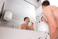 Bottom view of young man shaving his face with a razer Stock Photo