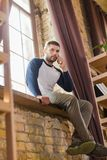 Bottom view of young man sitting on windowsill. Royalty Free Stock Image