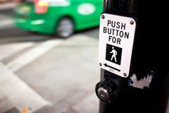 Bottone di attraversamento e taxi verde Immagine Stock Libera da Diritti
