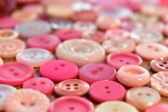 Bottone di cucito rosa luminoso su una tavola di legno Fotografia Stock