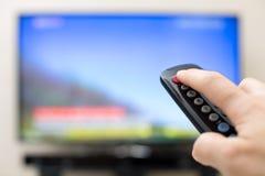Bottone di potere che preme sul telecomando della TV Fotografia Stock