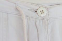 Bottone e cordone del dettaglio del tessuto dell'abbigliamento fotografia stock