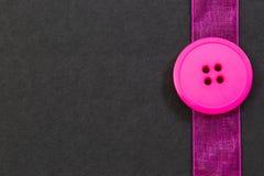 Bottone e nastro rosa sul nero Fotografia Stock