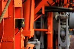 Bottone giallo contro il fondo vago dell'attrezzatura industriale Fotografia Stock