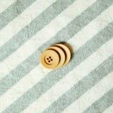 Bottone semplice beige sul fondo del panno del modello della banda Fotografie Stock Libere da Diritti