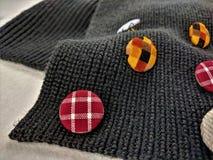 Bottoni colorati disposti sulla sciarpa grigia immagini stock libere da diritti