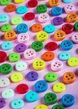 Bottoni dei colori differenti su un fondo rosa Fotografie Stock Libere da Diritti