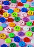 Bottoni dei colori differenti su un fondo rosa Fotografia Stock Libera da Diritti