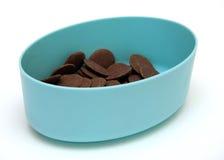 Bottoni del cioccolato al latte in un contenitore blu Fotografie Stock