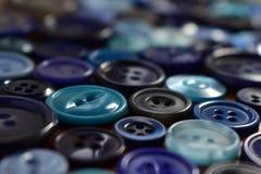 Bottoni di cucito blu su una tavola di legno Fotografia Stock