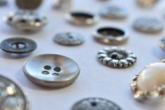 Bottoni di cucito d'argento su bianco Fotografie Stock