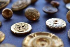Bottoni di cucito dell'oro su un fondo blu Immagine Stock Libera da Diritti