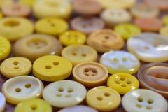 Bottoni di cucito gialli su una tavola di legno Fotografia Stock