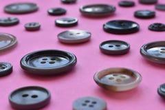 Bottoni di cucito grigi sul rosa Fotografie Stock