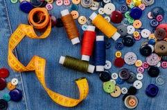Bottoni di cucito, nastro di misurazione giallo e bobine del filo Fotografia Stock