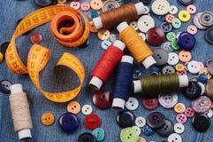 Bottoni di cucito, nastro di misurazione giallo e bobine del filo Vista superiore Immagini Stock