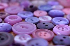 Bottoni di cucito porpora su una tavola di legno Fotografia Stock