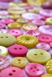 Bottoni di cucito rosa e gialli luminosi Fotografia Stock