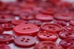 Bottoni di cucito rossi su bianco Immagine Stock