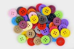 Bottoni di plastica variopinti su un fondo bianco Fotografia Stock