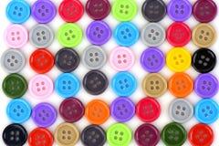 Bottoni di plastica variopinti su un fondo bianco Immagine Stock Libera da Diritti