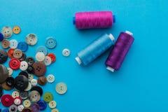 Bottoni e filo su un fondo blu Fotografia Stock