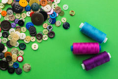Bottoni e filo su un fondo verde Immagine Stock