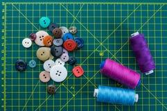 Bottoni e filo su un taglio della stuoia Fotografia Stock