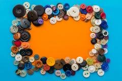 Bottoni e foglio di carta arancio su un fondo blu Immagine Stock Libera da Diritti