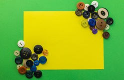 Bottoni e foglio di carta giallo su un fondo verde Fotografia Stock Libera da Diritti