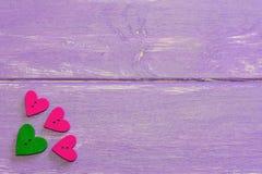 Bottoni a forma di del cuore Bottoni di legno su un fondo di legno porpora Bottoni di giorno di biglietti di S. Valentino messi V Immagini Stock