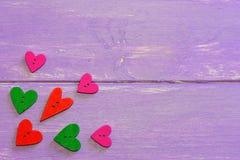 Bottoni a forma di del cuore variopinto Bottoni di legno del cuore di amore in vari colori Fondo di legno porpora con lo spazio d Fotografie Stock Libere da Diritti