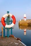 Bouée de durée blanche et rouge dans le port avec le phare Images libres de droits