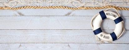 Bouée de sauvetage d'accueil à bord - avec le texte sur le fond en bois Photographie stock libre de droits
