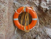 Bouée de sauvetage du plastique de mousse accrochant sur le mur en pierre Photo libre de droits