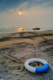Bouée de sauvetage et plage sauvage sous le coucher du soleil Photographie stock libre de droits