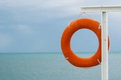 Bouée de sauvetage orange sur la côte Photographie stock libre de droits