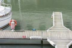 Bouée de sauvetage simple sur un croisement dockway à un port photographie stock