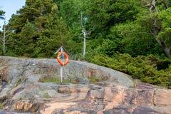 Bouée de sauvetage sur un rivage rocheux Photo libre de droits