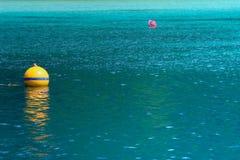 Bouée jaune sur la mer de turquoise Photographie stock