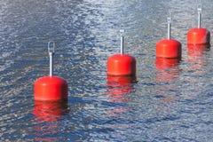 Bouées d'amarrage rouges dans une rangée, marina européenne photographie stock libre de droits