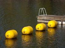 Bouées jaunes et dock en bois Photographie stock libre de droits