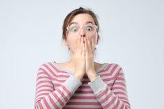 Bouche de bâche de femme avec la main et regarder fixement la caméra images stock